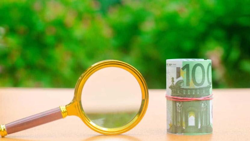 Проверка под лупой купюры 100 евро